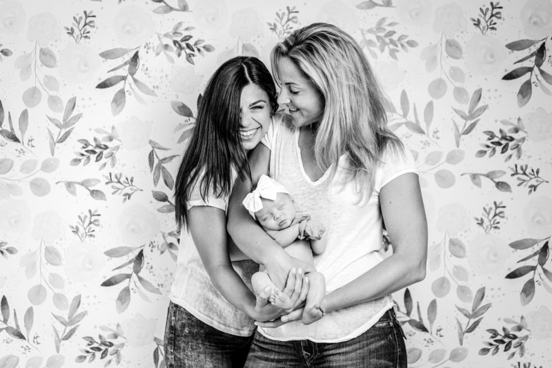 black and white photo of same sex couple smiling and holding their newborn baby