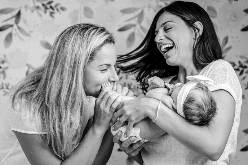 one mom laughs with her newborn baby in her arms and her wife kisses its feet