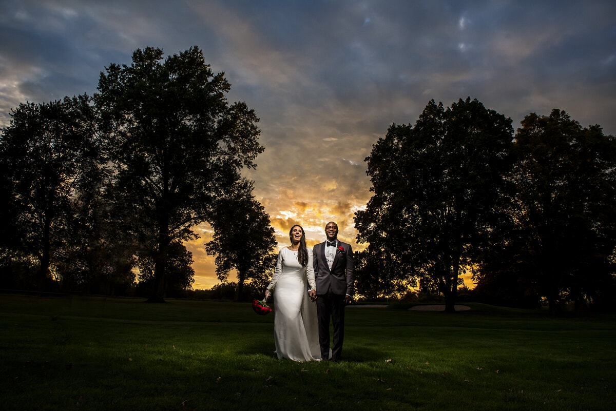wedding couples poses outdoors in front of trees and sunset