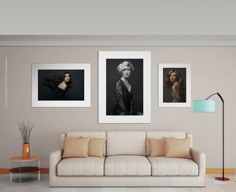 matted printed photographs on wall above couch