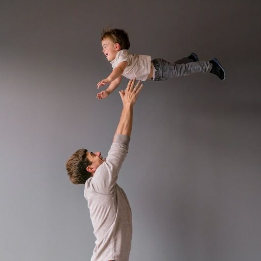 family photo shoot dad tosses son in the air